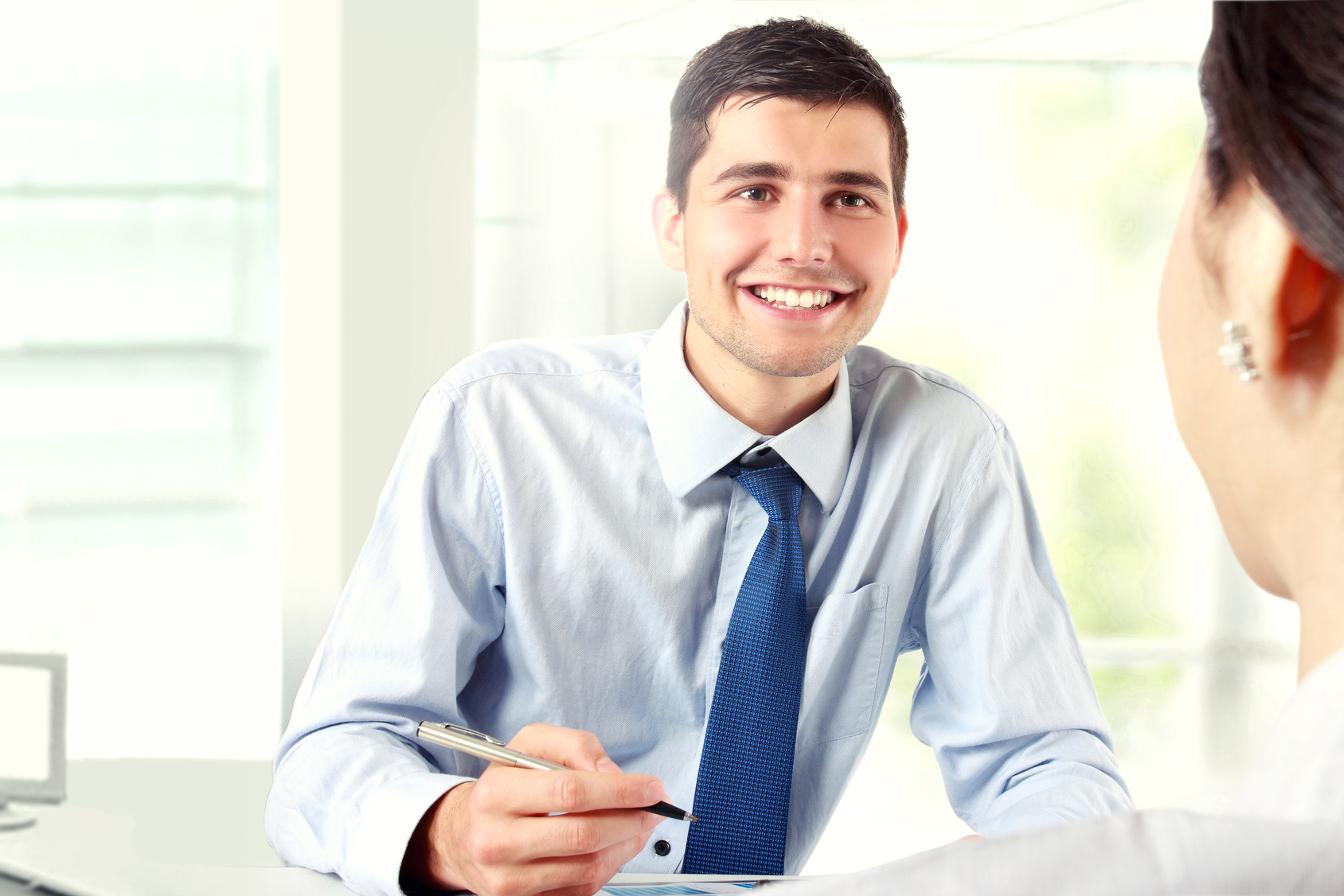 Image of young businessman interviewing female